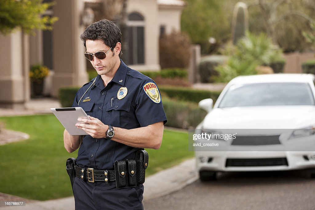 Law Enforcement Officer Using Computer Tablet : Stock Photo