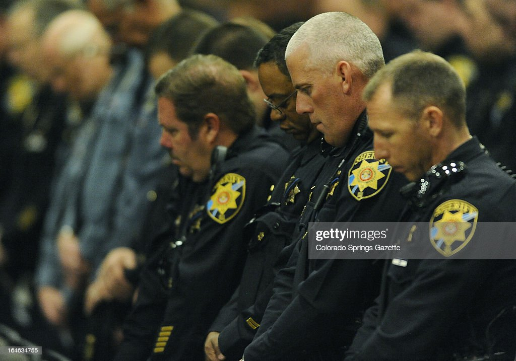 Law enforcement officers bow their head during a memorial for Tom Clements. The public memorial for the chief executive of the Department of Corrections was held at New Life Church in Colorado Springs, Colorado on Monday, March 25, 2013. Clements was shot and killed on the doorstep of his home last week in Monument, Colorado.