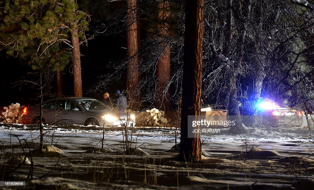 Law enforcement officers check cars at the roadblock near Angeles Oaks during a standoff with fugitive ex-cop Christopher Dorner, near San Bernardino, California on February 12, 2013. Nobody has yet been found in a burnt-out US mountain cabin where Dorner was believed to have barricaded himself after a six-day manhunt, a police spokesman said. Media reports that a body had been found in the cabin near Big Bear, east of Los Angeles, and identified as Dorner's were false, said Los Angeles Police Department (LAPD) spokesman Andrew Smith. AFP PHOTO /JOE KLAMAR