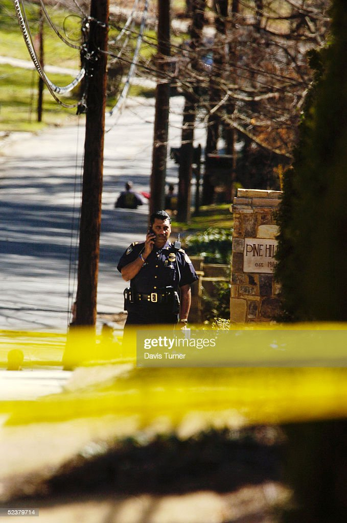 Law enforcement officers cover a crime scene at the corner of Canter Road and Lennox Road where an Atlanta customs agent was found shot to death...
