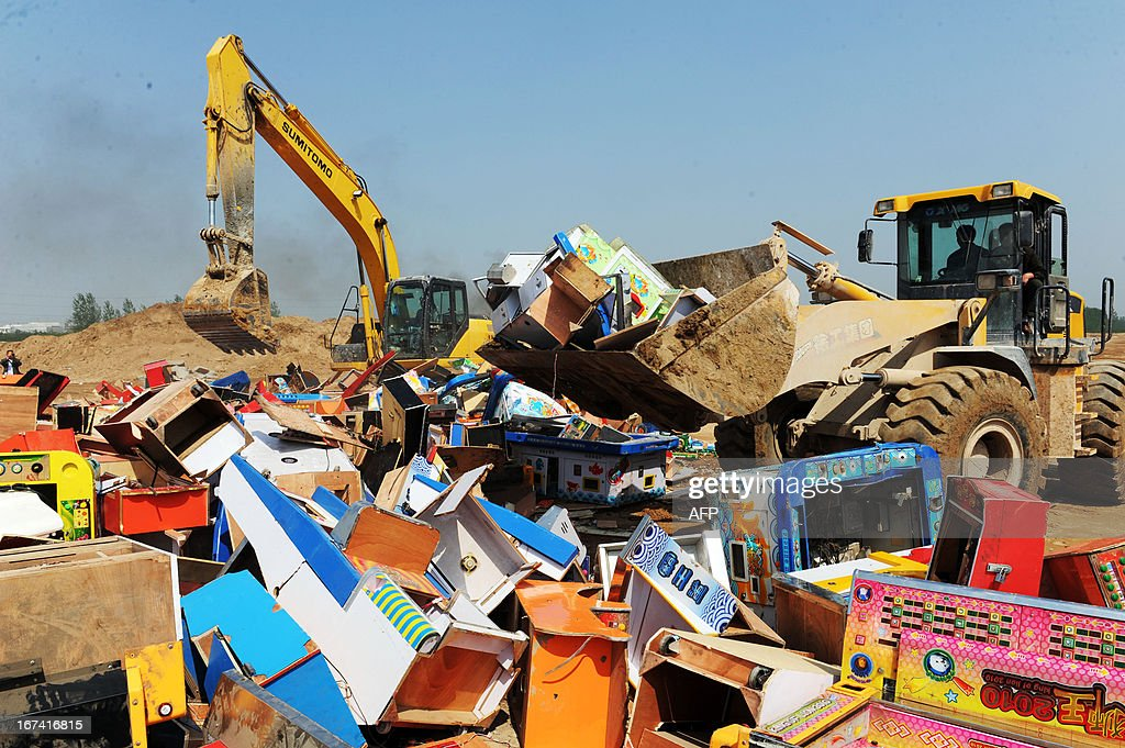 Law enforcement officers destroy illegal items such as gambling machines and publications in Bozhou, central China's Anhui province on April 25, 2013. As part of the Intellectual Property Day activities, this event is aimed at 'cleansing the social environment', local media reported. CHINA