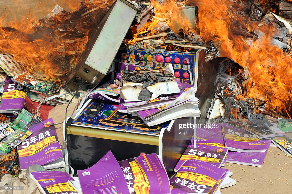 Law enforcement officers destroy illegal items, such as publications and gambling machines in Bozhou, central China's Anhui province on April 25, 2013. As part of the Intellectual Property Day activities, this event is aimed at 'cleansing the social environment', local media reported. CHINA