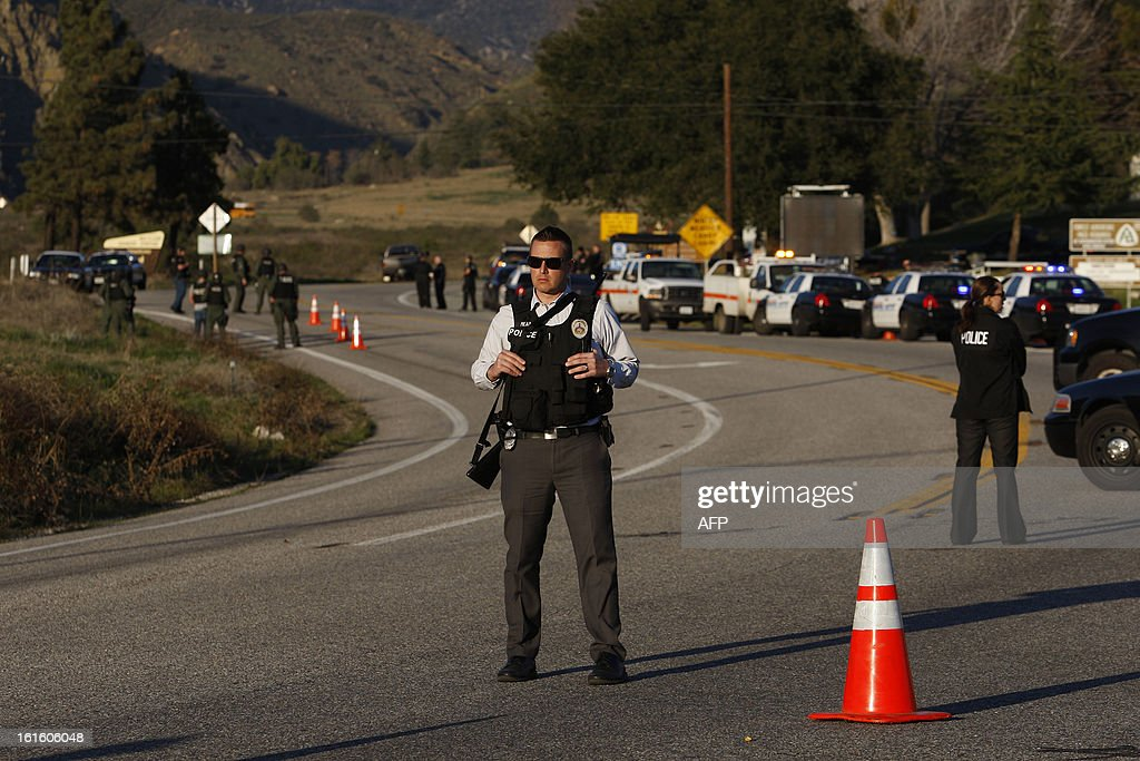 Law enforcement officers monitor a police roadblock on Highway 38, which leads to the Big Bear Lake, California, as a standoff with the former Los Angeles police officer who is now-quadruple murder suspect Christopher Dorner continues, near San Bernardino, California February 12, 2013, some 46 miles (75 km) from the San Bernardino Mountains near Big Bear, California where Dorner, a former US cop, has barricaded himself in a cabin and exchanged gunfire with police who have the cabin surrounded. AFP PHOTO / David McNew