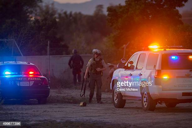 Law enforcement officers search for a possible suspect following a shootout with suspects of a mass shooting at the Inland Regional Center by...