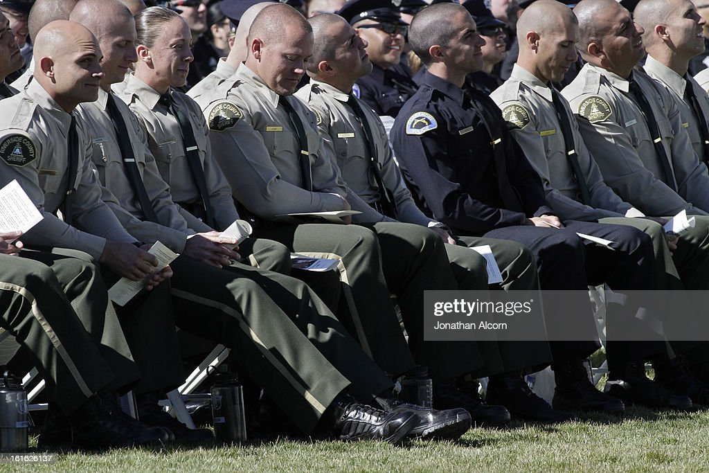 Law enforcement officers sit together during the funeral service for Riverside police Officer Michael Crain at Grove Community Church in Riverside, California, February 13, 2013. Officer Crain was allegedly killed by ex LAPD officer Chris Dorner on February 7, 2013.