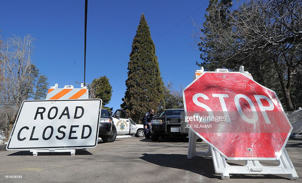 Law enforcement officers watch a roadblock as they continue the closure of Highway 38 at Angelus Oaks, California, on February 13, 2013. A former US cop wanted for at least three murders is thought to have died at the scene of a shootout with police but his remains must still be identified, officials said February 13. Police discovered human remains in the charred ruins of a cabin after a fire erupted during an intense gunbattle in the snowy mountains east of Los Angeles, where fugitive Christopher Dorner was thought to have taken refuge.