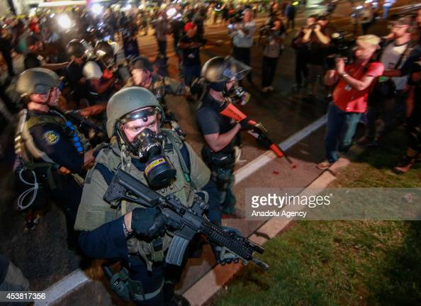Law enforcement officers watch on during a protest on August 18 2014 for Michael Brown who was killed by a police officer on August 9 in Ferguson...