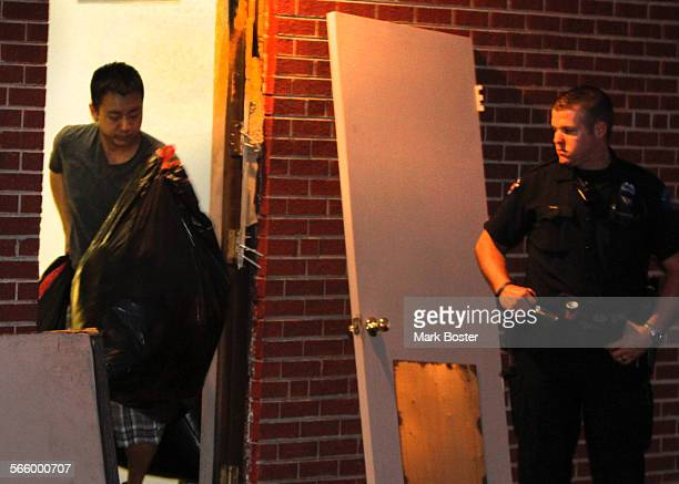 Law enforcement officials allow residents to retrieve their belongings from the apartment building in Aurora Colorado where mass shooting suspect...