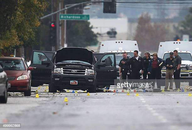 Law enforcement officials continue their investigation around the Ford SUV vehicle at the scene where suspects of the shooting at the Inland Regional...