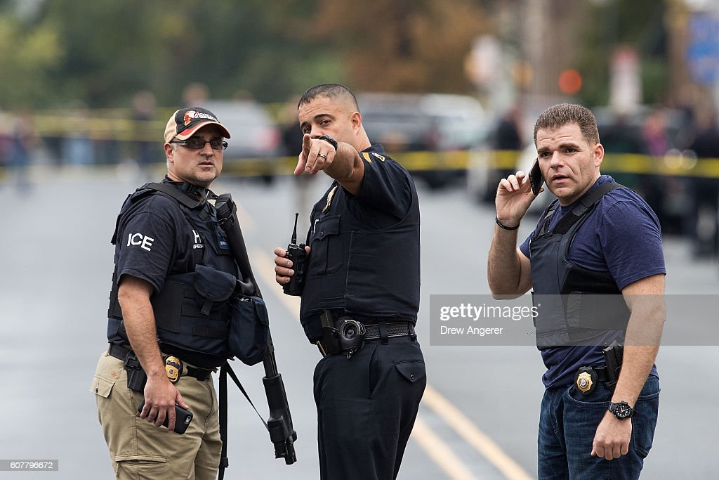 Law enforcement officials gather at the site where Ahmad Khan Rahami, who was wanted in connection to Saturday night's bombing in Manhattan, was arrested after a shootout with police, September 19, 2016 in Linden, New Jersey. On Monday morning, law enforcement released a photograph of 28-year-old Ahmad Khan Rahami, who they are seeking in connection to the attack.