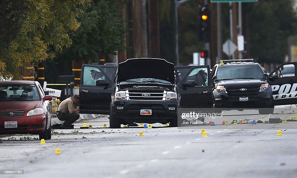 Law enforcement officials invesigate around the Ford SUV vehicle that was the scene where suspects of the shooting at the Inland Regional Center were...