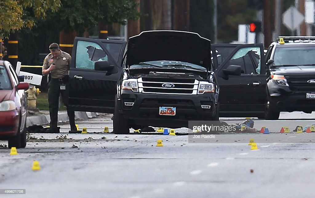Law enforcement officials investigate around the Ford SUV vehicle that was the scene where suspects of the shooting at the Inland Regional Center...
