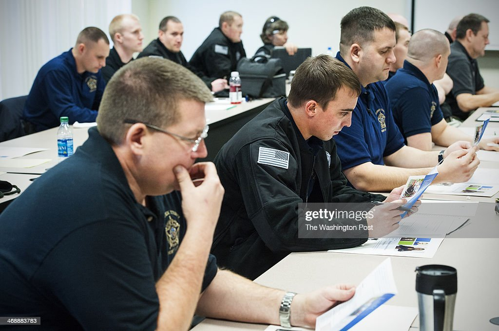 Law enforcement officials look over handout material prior to a four hour class at the Public Safety Training Facility Tuesday February 11, 2014 in Frederick, MD. A year after a 26-year-old man with Down syndrome died while three off duty Frederick County deputies forced him from a movie theater, the Sheriff's office has adopted a training program specifically aimed at teaching law enforcement officials how best to interact with individuals with intellectual disabilities.