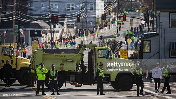 Law enforcement officials media runners administrators and volunteers mill about prior to the start of the Boston Marathon on April 21 2014 in...