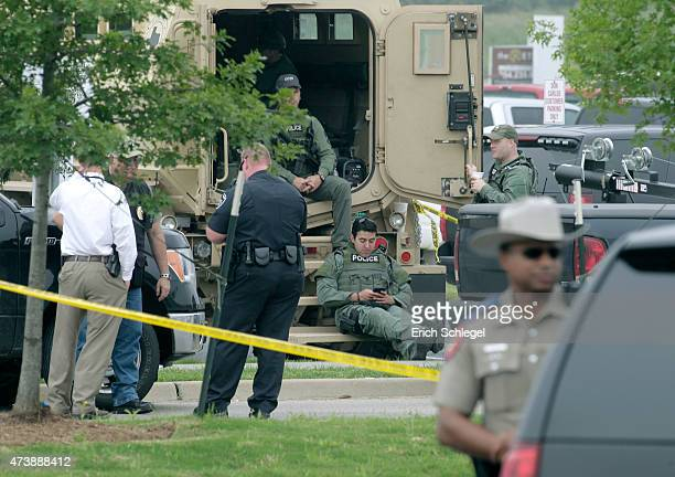 Law enforcement officials sit at the scene of a motorcyle gang shootout theTwin Peaks restaurant May 18 2015 in Waco Texas A shootout between rival...