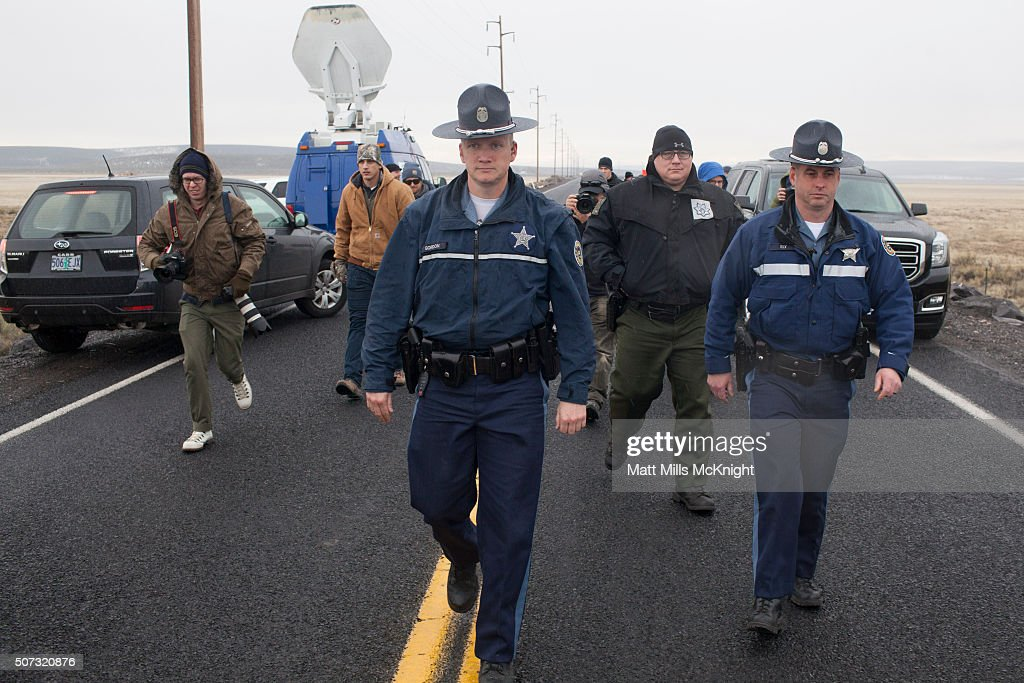 Law enforcement officials walk along the highway where media gathered near a checkpoint at the Malheur National Wildlife Refuge January 28 2016 near...