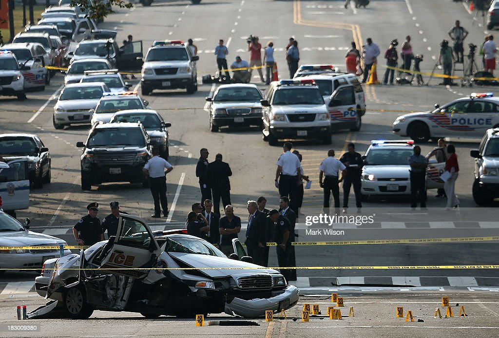 Law enforcement personnel gather around a police vehicle that was involved in an incident with another vehicle on Constitution Avenue outside the U.S. Capitol October 3, 2013 in Washington, DC. Capitol police locked down the facility during the incident.