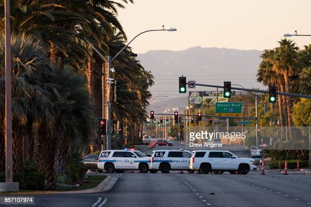 Law enforcement vehicles gather near one of the entrance points to the concert venue where Sunday night's mass shooting October 3 2017 in Las Vegas...