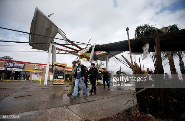 Law enforcement walk through a damaged gas station along Chef Menteur Highway after a tornado touched down in the eastern part of the city on...