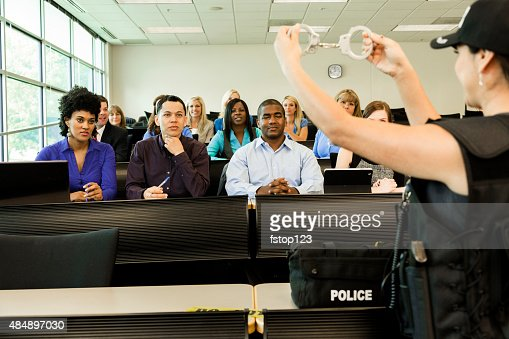 Law:  Policewoman speaks to police cadets in classroom. Handcuffs