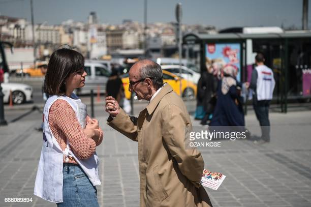 A law student explains a man about the new constitution proposal on April 11 2017 at Eminonu district in Istanbul as the countdown starts for the...