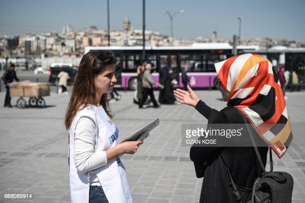 A law student speaks with a woman about the new constitution proposal on April 11 2017 at Eminonu district in Istanbul as the countdown starts for...