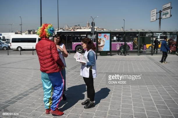 Law students explain a man wearing clown clothes about the new constitution proposal on April 11 2017 at Eminonu district in Istanbul as the...