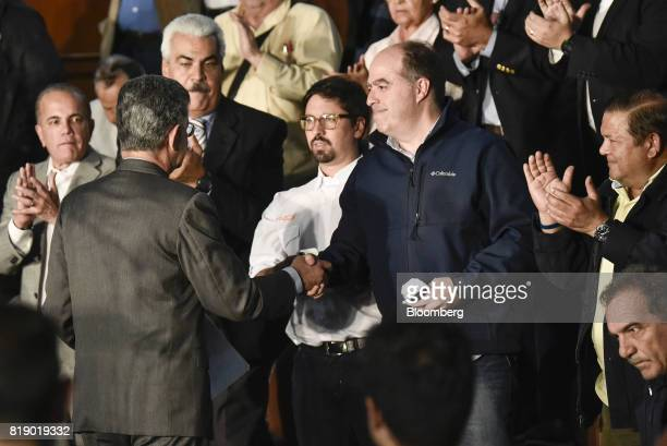 Lawmaker Henry Ramos Allup left shakes hands JulioBorges president of the opposition controlled National Assembly during a press conference held by...
