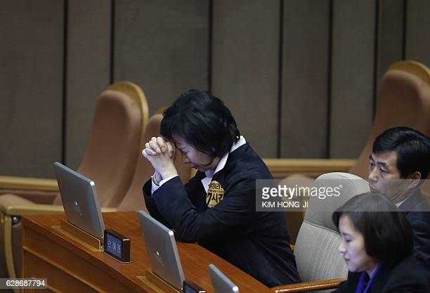 TOPSHOT A lawmaker prays after voting on the impeachment bill of South Korean President Park Geunhye at the National Assembly in Seoul South Korea...