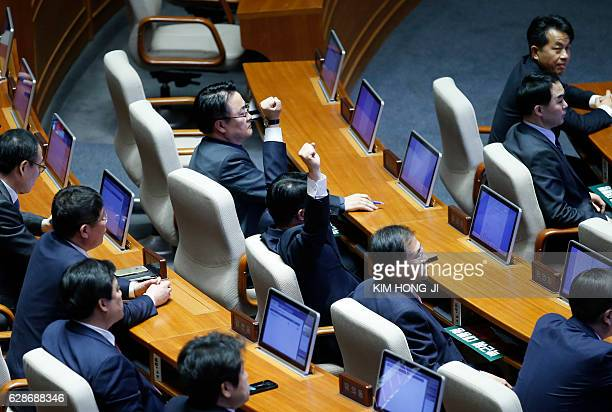 TOPSHOT A lawmaker reacts after impeachment vote on South Korean President Park Geunhye was passed at the National Assembly in Seoul South Korea...