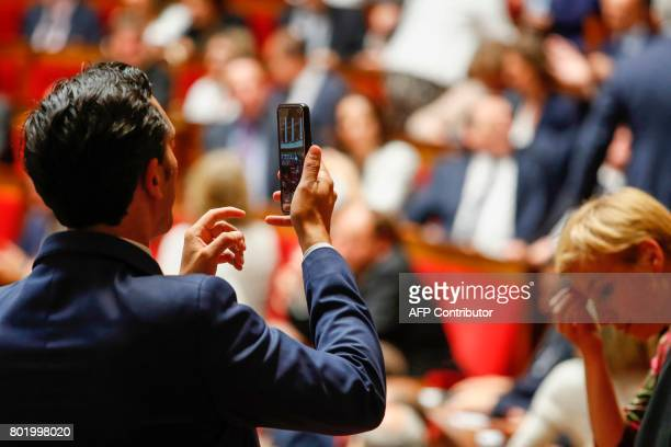 A lawmaker takes a photo with his mobile phone during the inaugural session of the 15th legislature of the French Fifth Republic at the National...