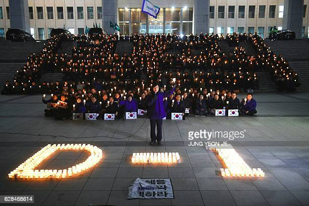 TOPSHOT Lawmakers and members of South Korea's main opposition Democratic Party hold candles at a protest urging the impeachment of President Park...