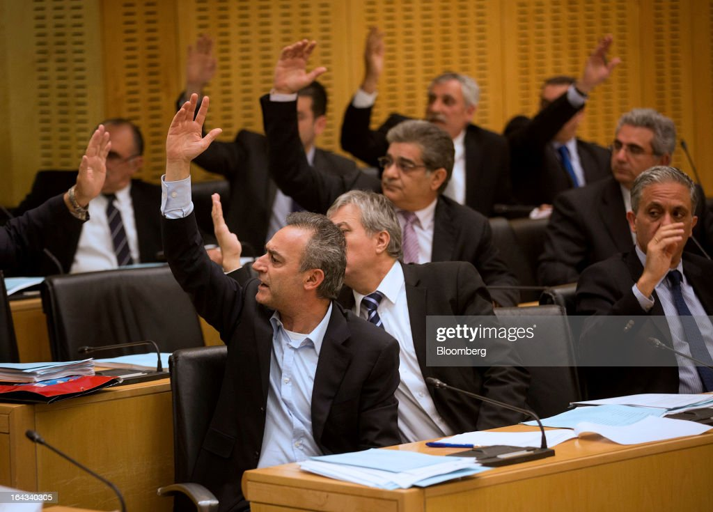 Lawmakers raise their hands to vote on the nation's banking crisis inside the Cypriot parliament in Nicosia, Cyprus, on Friday, March 22, 2013. The aid package Cyprus is seeking would only provide temporary relief as it risks triggering a capital flight that would push the nation closer to needing to restructure its debts. Photographer: Simon Dawson/Bloomberg via Getty Images