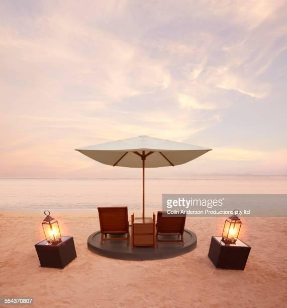 Lawn chairs under umbrella on tropical beach