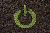 Lawn in the shape of the power button on the soil