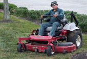 A lawn mower operator from a landscaping company mows the lawn August 7 in Fairfax Virginia AFP PHOTO/Paul J Richards