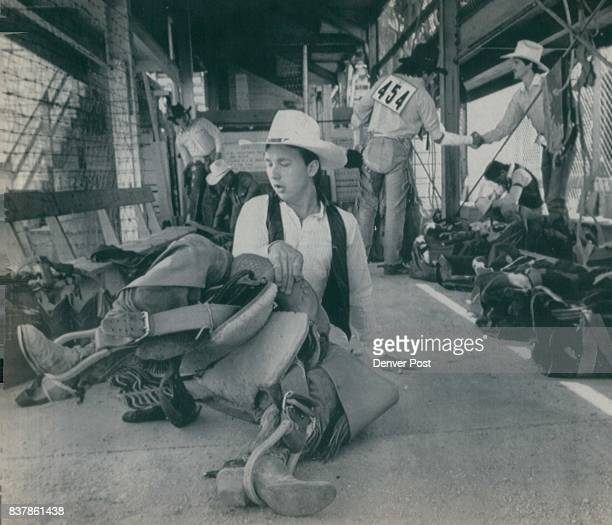 """Lawrence Bishop a Middleton Ohio cowboy resins his saddle while warming up on the floor of the 'ready"""" area behind the chutes Bishop was readying..."""