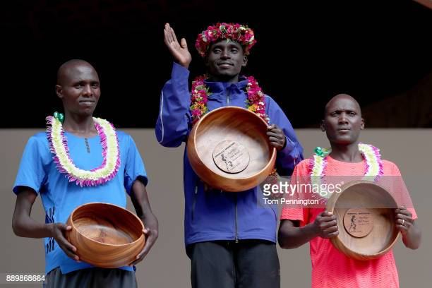 Lawrence Cherono of Kenya in second place Dennis Kimetto of Kenya in first place and Titus Ekiru in third place pose during the awards ceremony after...