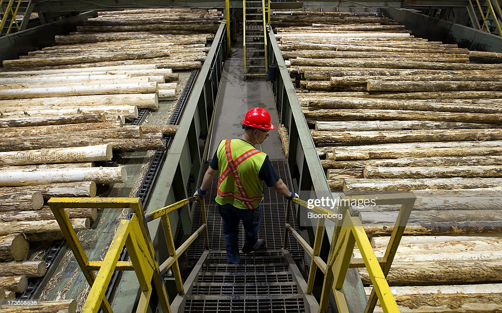 Lawrence Lust, superintendent of the West Fraser Timber Co. sawmill, monitors logs on the production line at the company's facility in Quesnel, British Columbia, Canada, on Thursday, July 11, 2013. West Fraser Timber Co., the largest lumber producer in North America, had a sustainable rise in price, demand volatility, and profits within the past year. Photographer: Ben Nelms/Bloomberg via Getty Images