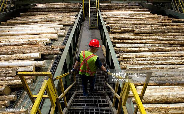 Lawrence Lust superintendent of the West Fraser Timber Co sawmill monitors logs on the production line at the company's facility in Quesnel British...