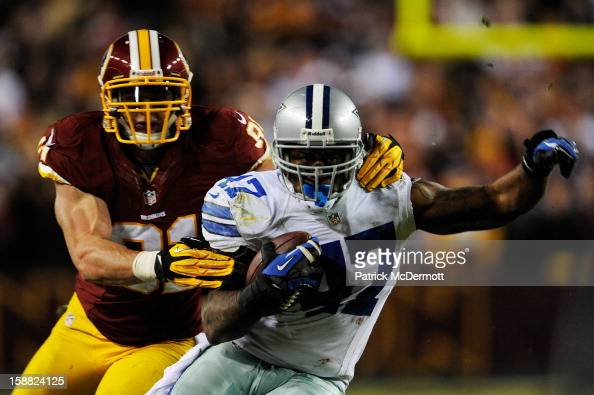 Lawrence Vickers of the Dallas Cowboys carries the ball against the defense of Ryan Kerrigan of the Washington Redskins at FedExField on December 30...