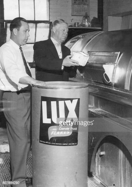 I H Lawson general superintendent of the CityElite laundry and J E Hollingsworth president of the firm load a giant washer at the company plant with...