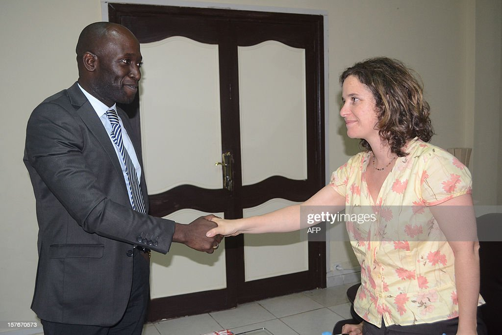Lawyer and senior counsel with the International Justice Program at Human Rights Watch, Elise Keppler (R), shakes hands with the Guinean Minister for Human Rights, Kalifa Gassama Diaby, before a press conference dedicated to a Human Rights Watch report on the 2009 massacre of opposition supporters by junta troops, in Conakry, on December 5, 2012. Human Rights Watch today called on Guinea to step up efforts to bring to justice those responsible for a stadium massacre in 2009 that left almost 160 people dead. A 2009 HRW investigation suggested that the 'killings, rapes and other abuses that security forces committed on and after September 28 (2009) rise to the level of crimes against humanity due to their widespread and systematic nature and evidence that the crimes were premeditated and organised', HRW said in a report today. The massacre occurred when a peaceful rally organised by the opposition in Conakry's biggest stadium was bloodily suppressed by junta troops, leaving 157 dead, hundreds of women victims of sexual violence and over a thousand people injured.