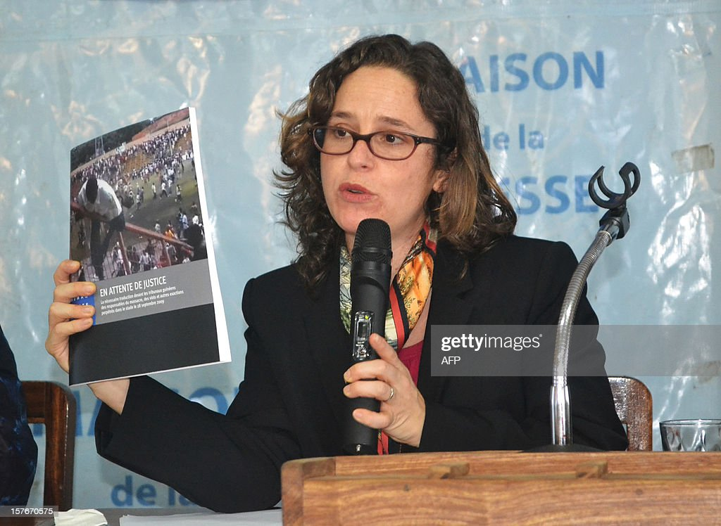 Lawyer and senior counsel with the International Justice Program at Human Rights Watch, Elise Keppler, holds a copy of a report on the 2009 massacre of opposition supporters by junta troops, as she speaks to journalists during a press conference marking the release of the report, in Conakry, on December 5, 2012. Human Rights Watch today called on Guinea to step up efforts to bring to justice those responsible for a stadium massacre in 2009 that left almost 160 people dead. A 2009 HRW investigation suggested that the 'killings, rapes and other abuses that security forces committed on and after September 28 (2009) rise to the level of crimes against humanity due to their widespread and systematic nature and evidence that the crimes were premeditated and organised', HRW said in a report today. The massacre occurred when a peaceful rally organised by the opposition in Conakry's biggest stadium was bloodily suppressed by junta troops, leaving 157 dead, hundreds of women victims of sexual violence and over a thousand people injured.