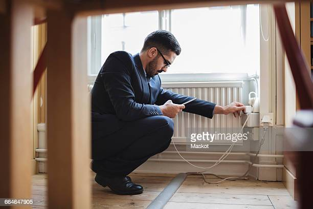 Lawyer crouching while charging phone by radiator with furniture in foreground