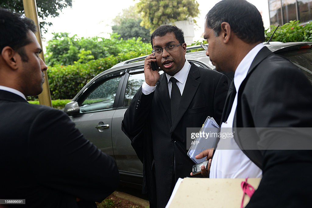 Lawyer for the impeached Sri Lankan chief justice Shirani Bandaranayake Saliya Peiris (C) speaks on a cellular telephone as he emerges from the Supreme Court Complex in Colombo on January 3, 2013, after a Supreme Court decision that virtually struck down a move by the ruling party to impeach the Chief Justice Shirani Bandaranayake. The Court held that parliament could not use its own standing orders to try the chief justice who faces allegations of misconduct from the ruling party after she struck down several bills of the government. AFP PHOTO/Ishara S