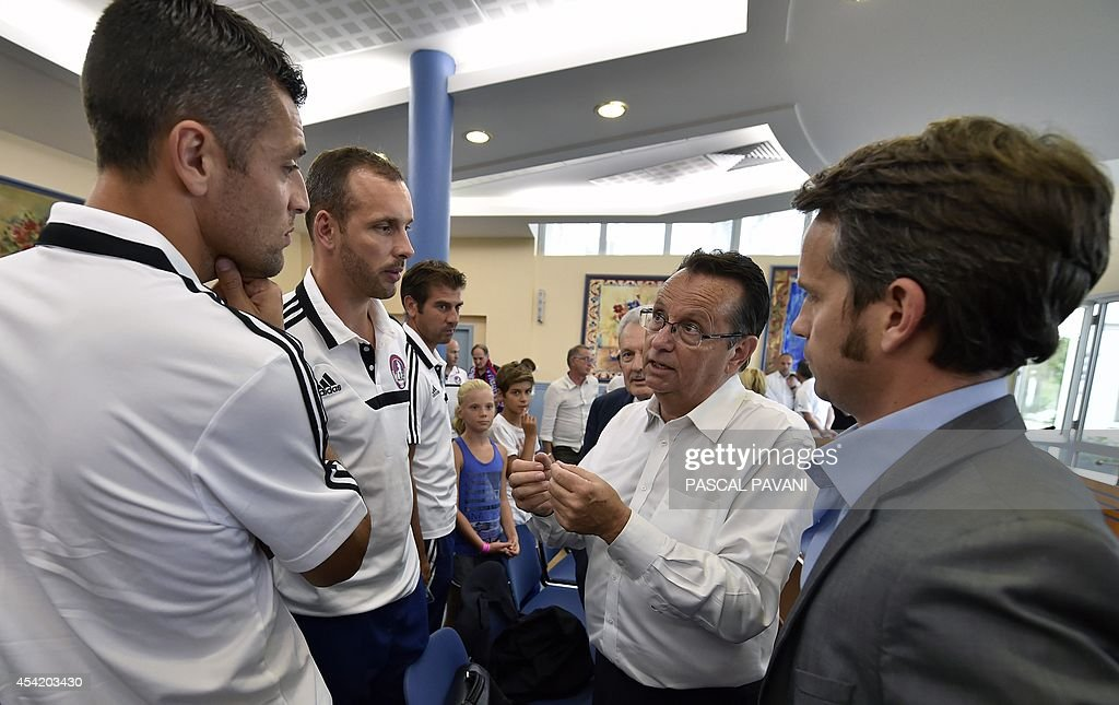 Lawyer of French football club Luzenac Ariege Pyrenees (LAP), Jean-Jacques Bertrand (R), speaks with the team's coach Nicolas Dieuze (L) and players, after a hearing on August 26, 2014 at the Toulouse administrative court, regarding the club's appeal against the ruling of French Professional Football League (LFP), which decided on August 8, 2014 not to allow the club to play in the French second division. The ruling said: 'The club does not have a ground which conforms to the required safety standards.' The LFP will review the case on August 27 and will decide if the club can integrate or not the French second division.