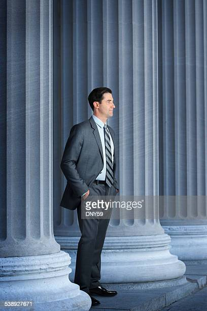 Lawyer Or Banker Standing Next To Large Columns