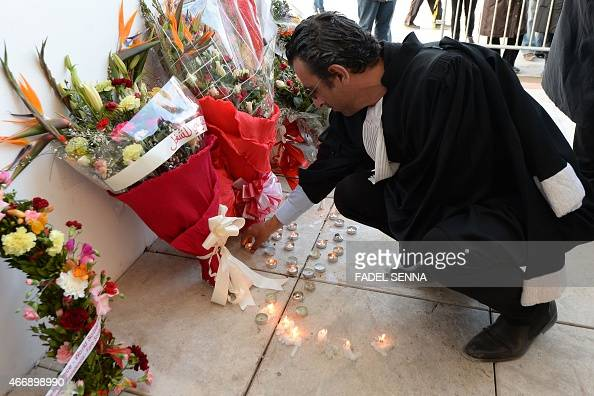 A lawyer places a lit candle on the floor in front of the National Bardo Museum in Tunis on March 19 2015 during a demonstration in solidarity with...