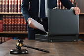 Midsection of lawyer putting documents in briefcase with gavel at desk in courtroom